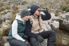 Couple sitting on rock with binoculars while on a hike Royalty Free Stock Images