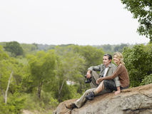 Couple Sitting On Rock And Enjoying The View Stock Photos
