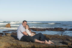 Couple sitting on a rock. Happy in love caucasian couple sitting together on the beach on a rock hugging Royalty Free Stock Photos
