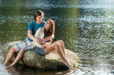 Couple sitting on rock by the lake Royalty Free Stock Photography