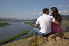 Couple sitting on a rock in mountains Stock Photo