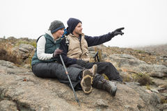 Couple sitting on rock with trekking poles while on a hike Stock Images