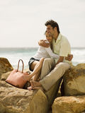 Couple sitting on the rocks at a beach Stock Images