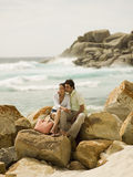 Couple sitting on the rocks at a beach. Stock Image