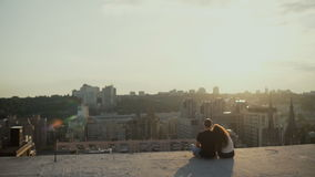 Couple sitting on the roof at sunset stock footage
