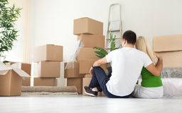 Couple sitting in room full of moving boxes. Couple sitting  and looking  lot of moving boxes, back view Royalty Free Stock Photos