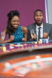 Couple sitting at roulette table waiting anxiously for wheel to stop spinning. In the casino Royalty Free Stock Photography