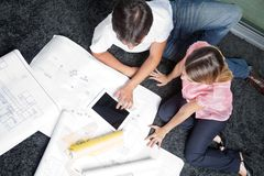 Couple Sitting On Rug With House Plans Royalty Free Stock Photo