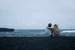 Couple sitting on the sand. Contemplating the ocean Stock Photography