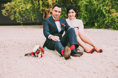 Couple sitting on sand near green bushes Royalty Free Stock Photography
