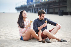 Couple sitting in sand at santa monica pier. Royalty Free Stock Photos
