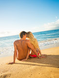 Couple sitting on a sandy tropical beach. Young couple sitting together on a sandy tropical beach Royalty Free Stock Image