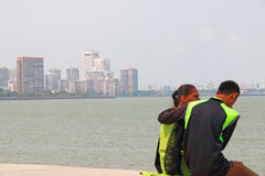 Couple sitting on sea wall with view of mumbai india Royalty Free Stock Photography