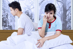 Couple sitting separately on bed Royalty Free Stock Image
