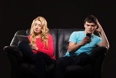 A couple sitting separately with smartphones. Boy and girl sitting separately with smarthones. Disinterest, apathy and alienation concept Stock Images