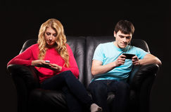 A couple sitting separately with smartphones. Boy and girl sitting separately with smarthones. Disinterest, apathy and alienation concept Royalty Free Stock Photo