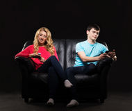 A couple sitting separately with smartphones Stock Photography
