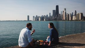 Couple sitting on shore of Michigan lake and eating breakfast. Man and woman have picnic near water in Chicago. stock footage
