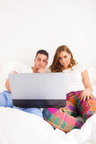 Couple sitting side by side in bed relaxing with computer Stock Photo