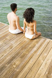 Couple sitting on the side of a wooden jetty by the sea, holding hands Stock Photos