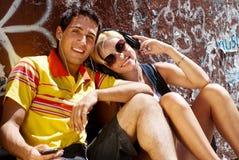 Couple sitting on sidewalk Royalty Free Stock Photo