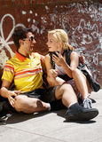 Couple sitting on sidewalk Stock Photography