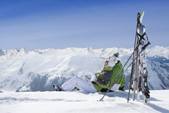 Couple sitting in snow on mountain top with skis royalty free stock photos