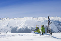 Couple sitting in snow on mountain top with skis stock photography