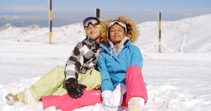 Couple sitting in snow on ski slope Royalty Free Stock Image