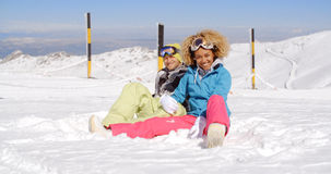 Couple sitting in snow on ski slope Royalty Free Stock Photography