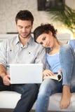 Couple sitting on sofa Stock Image