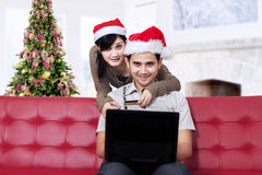 Couple sitting on sofa and buy online Royalty Free Stock Images