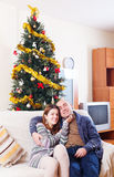 Couple sitting on sofa at Christmas time Stock Images