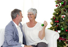 Couple sitting on sofa with a Christmas tree Stock Images