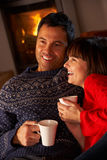 Couple Sitting On Sofa By Cosy Log Fire. Middle Aged Couple Sitting On Sofa By Cosy Log Fire With Hot Drink Laughing With Each Other Royalty Free Stock Photography