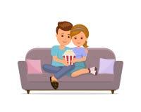 Couple sitting on sofa cuddling, eating popcorn and watching TV. Stock Photo