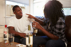 Couple Sitting On Sofa Drinking Alcohol And Arguing. Shouting At Each Other stock photo