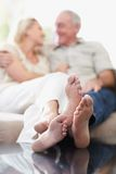 Couple sitting on sofa with feet propped on table Stock Photo