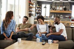 Couple Sitting On Sofa With Friends At Home Talking Royalty Free Stock Image