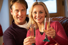 Couple Sitting On Sofa With Glasses Of Champagne Stock Image