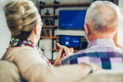 Couple sitting on a sofa holding remote home control system on a digital tablet royalty free stock image