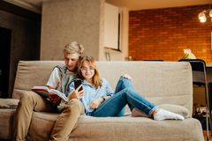 Couple sitting on sofa, leisure together, man reading book, woman using phone Royalty Free Stock Photo