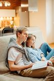 Couple sitting on sofa, leisure together, man reading book, woman using phone Stock Image