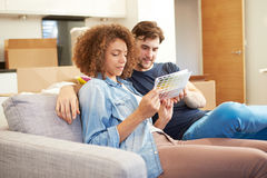 Couple Sitting On Sofa Looking At Paint Charts Stock Image