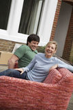 Couple Sitting On Sofa Outdoors Stock Images