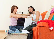 Couple sitting  on sofa and packing suitcase at home Stock Images