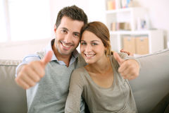 Couple sitting in sofa with a positive look. Young couple showing thumbs up Stock Image
