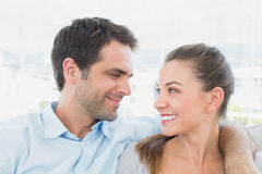 Couple sitting on the sofa smiling at each other Stock Images