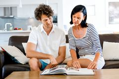 Couple at home with a book. Couple sitting on sofa and studying book together Royalty Free Stock Photo