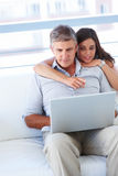 Couple sitting on a sofa and surfing on laptop Royalty Free Stock Image